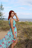 Redhead girl in long dress standing at the seashore Stock Image