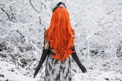 Redhead girl with long hair stand back on winter background. Winter snow fall. Redhead woman in black retro dress and with long gl royalty free stock photo