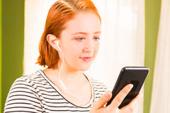 Redhead Girl Looking at Cellphone Stock Image