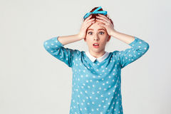 Redhead girl looking desperate and panic, holding hands on her head, screaming with mouth wide open. royalty free stock photo