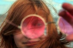 Redhead girl looking through rose-colored glasses royalty free stock photography