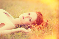 Redhead girl. Lying down on grass. Autumn Royalty Free Stock Photography
