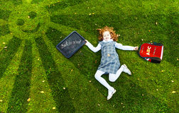 Redhead girl lying on the green grass in park, high top view. Stock Image
