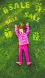 Redhead girl lying on the green grass in park. Royalty Free Stock Photo