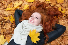 Redhead girl lying on leaves in city park, fall season Stock Photography