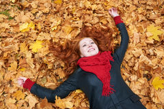 Redhead girl lying on leaves in city park, fall season Stock Photo