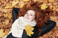 Redhead girl lying on leaves in city park, fall season Royalty Free Stock Photography