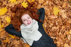 Redhead girl lying on leaves and wink in city park, fall season Royalty Free Stock Photo