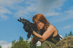 Redhead girl military aim from the weapon Royalty Free Stock Photography