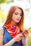 Redhead girl with mobile phone Royalty Free Stock Photo