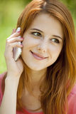 Redhead girl with mobile phone at the park. Stock Photos