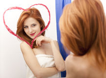 Redhead girl near mirror Royalty Free Stock Image