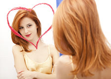Redhead girl near mirror Royalty Free Stock Photography