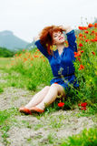 Redhead girl near the poppy field Stock Photography