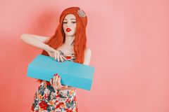 Redhead girl open a gift box for the holiday. Woman with long red hair in trendy summer dress with blue present box on pink backgr. Ound. Present gift on stock photography