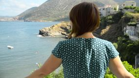 Redhead girl opens onto a balcony of hotel and looking at the blue sea stock video