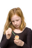Redhead girl is painting an egg holder. Isolated on white royalty free stock photo