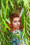 Redhead girl in park. Girl with red curly hair and blue floral dress looking over her shoulder surrounded by weeping willow leaves Stock Photo