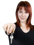 Redhead girl passing keys. Cute smiling redhead girl holding keys towards the camera Stock Photos