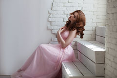 Redhead girl in pink dress sitting on the stairs Stock Images