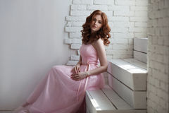Redhead girl in pink dress sitting on the stairs Royalty Free Stock Photos