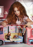 Redhead girl playing in a doll house. And dolls on the bed she is sitting and reading a book, children's fantasy, concept doll house Stock Photo