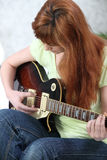 Redhead girl playing guitar Royalty Free Stock Photos