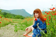 Redhead girl in poppy field Royalty Free Stock Photos