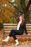 Redhead girl portrait in city park, fall season Royalty Free Stock Photos