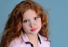 Redhead girl. Portrait of a redheaded girl on a blue background Royalty Free Stock Image