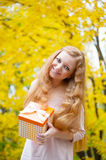 Redhead girl with present box in autumn park Stock Image