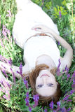 Redhead girl in purple flowers. Royalty Free Stock Image