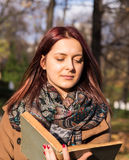 Redhead girl reading book in park Stock Images