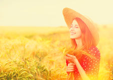 Redhead girl in red dress. On wheat field Royalty Free Stock Images