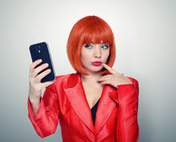 Redhead girl in red photographs himself on smartphone Royalty Free Stock Images