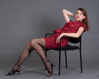 Redhead girl relaxing on a chair Stock Image