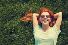 Redhead girl relaxing on the grass. Relaxing redhead girl lying on the grass. woman in sunglasses relaxation outdoor. photo with artistic effect. vintage toning Stock Photography