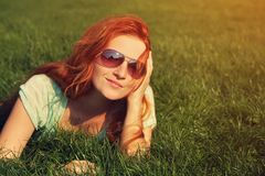 Redhead girl relaxing on the grass. Relaxing redhead girl lying on the grass. woman in sunglasses relaxation outdoor. photo with artistic effect. vintage toning Royalty Free Stock Photography