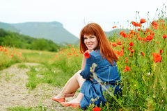 Redhead girl is resting. Near the poppy field Stock Images