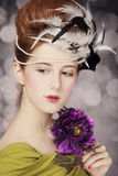 Redhead girl with Rococo hair style and flower at vintage background. Photo in old style. royalty free stock photography