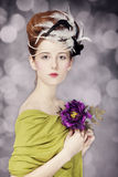 Redhead girl with Rococo hair style and flower at vintage background. Photo in old style. stock photo