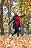 Redhead girl run with leaf bouquet in city park, fall season Stock Images