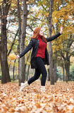 Redhead girl run with leaf bouquet in city park, fall season Royalty Free Stock Images