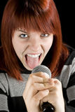 Redhead girl screaming in microphone. A happy redhead girl holding a karaoke microphone and screaming Royalty Free Stock Photos