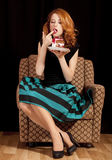 Redhead girl secretly eating cake. Stock Photography