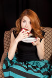 Redhead girl secretly eating cake. Stock Photo