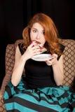Redhead girl secretly eating cake. Stock Photo