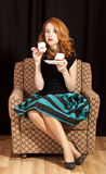 Redhead girl secretly eating cake. Royalty Free Stock Photos