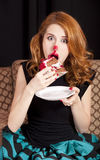Redhead girl secretly eating cake. Stock Image