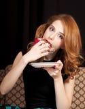 Redhead girl secretly eating cake. Royalty Free Stock Images